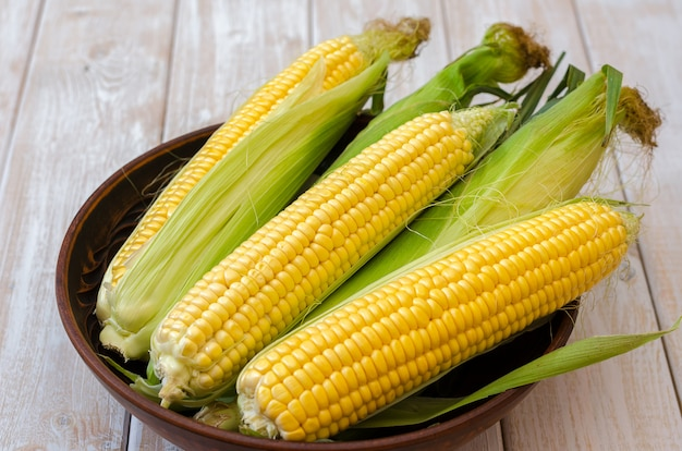 Ripe corn in a clay bowl on a light wooden background. Premium Photo