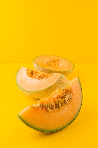 Ripe fresh cantaloupe slices on yellow background Free Photo