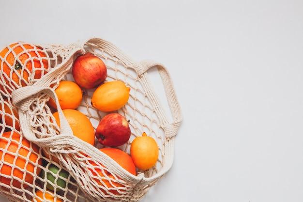 Спелые плоды в сеточку крючком на белом пространстве. концепция здорового образа жизни. концепция доставки. Premium Фотографии