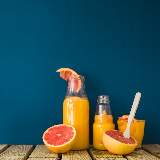 Ripe grapefruits with glass and bottles of juice on wooden table Free Photo