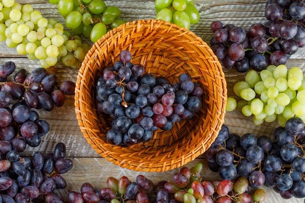 Спелый виноград в плетеной корзине на деревянном фоне. плоская планировка. Бесплатные Фотографии