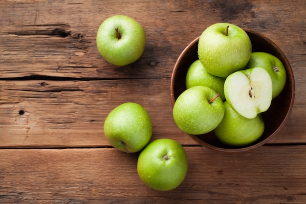 Ripe green apples in a wooden bowl. Premium Photo