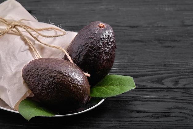 Спелые плоды авокадо haas. аллигаторная груша. авокадо с черной кожурой. продукты для правильного питания. Premium Фотографии