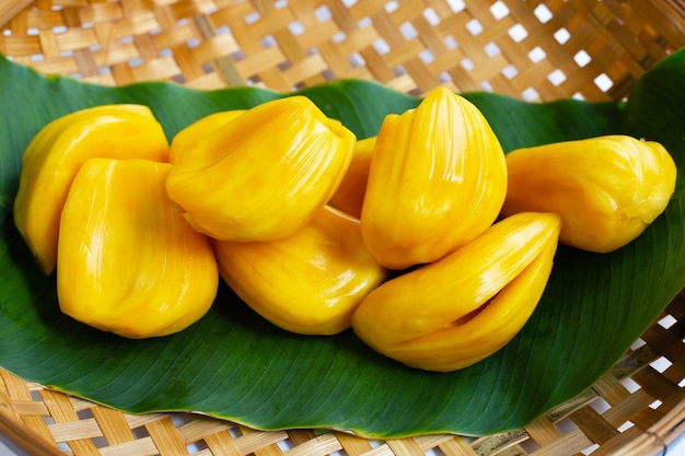 木製の竹の脱穀バスケットのバナナの葉に熟したジャックフルーツ Premium写真