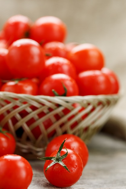 Ripe and juicy cherry tomatoes with drops of moisture in a wicker basket. old wooden table, around the canvas of burlap Premium Photo