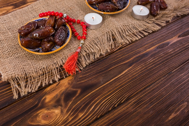 Ripe juicy dates plate with red prayer beads with lighted candles on jute tablecloth over the wooden desk Free Photo