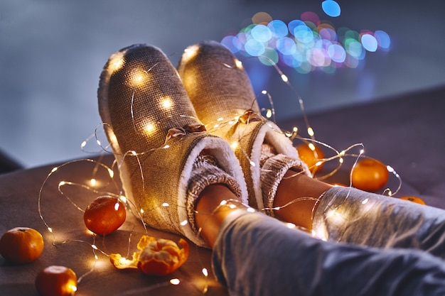 Спелые оранжевые мандарины, теплые белые гирлянды из рождественских огней и женские ножки в теплых пушистых мягких зимних тапочках в уютном доме в канун рождества Premium Фотографии
