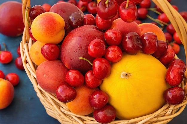 Ripe organic fruits sweet cherries nectarines apricots melon in wicker basket Premium Photo