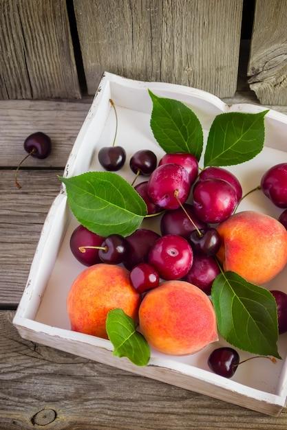 Спелые персики, сливы и вишня в коробке Premium Фотографии
