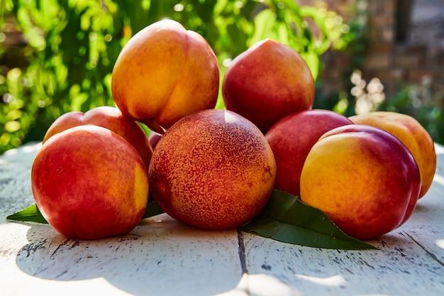 古い木製のテーブルの上の葉を持つ熟した桃 Premium写真