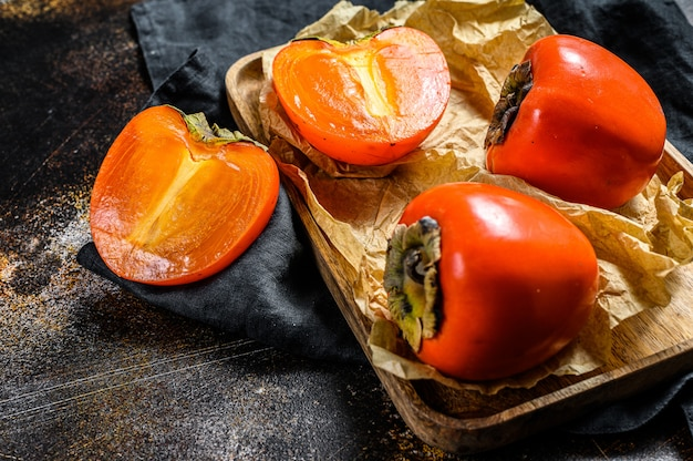 Ripe persimmon on a wooden tray in parchment paper. top view Premium Photo
