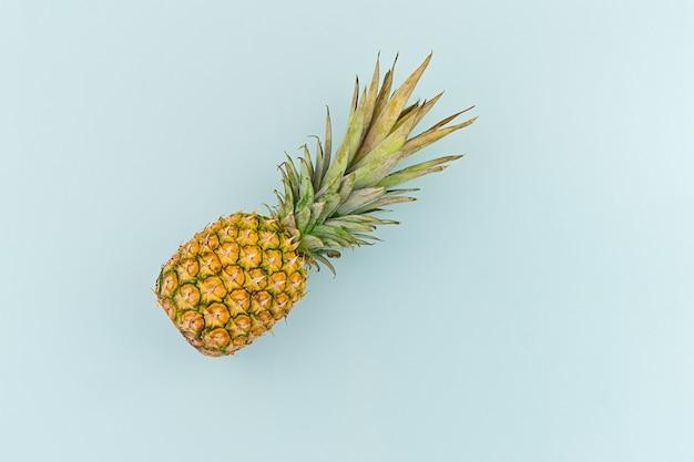 Ripe pineapple on blue background in minimalism style Premium Photo