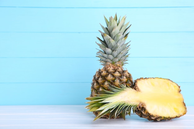 Ripe pineapple and half of pineapple on a blue wooden background Premium Photo