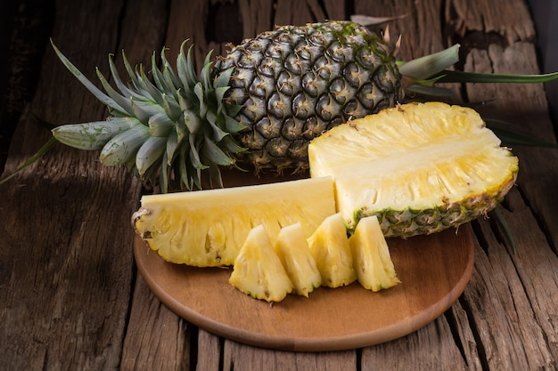 Ripe pineapple and pineapple slices on a wooden background tropical fruits Premium Photo