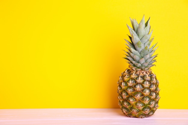 Ripe pineapple on a yellow background with copy space Premium Photo