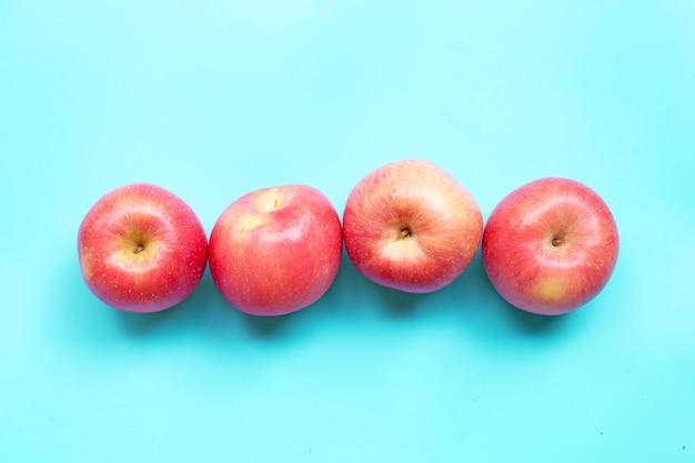 Спелые розовые яблоки на синем фоне. вид сверху Premium Фотографии