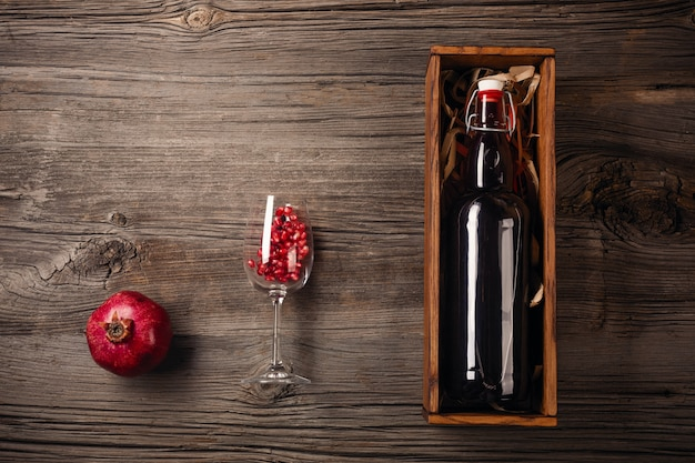 Ripe pomegranate fruit with a glass of wine, a bottle in a box on a wooden background Premium Photo