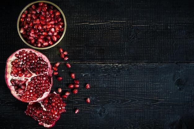 Ripe pomegranate, pomegranate kernels on black wooden. Premium Photo
