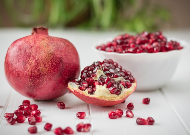 Ripe pomegranate seeds on a white wooden table Premium Photo