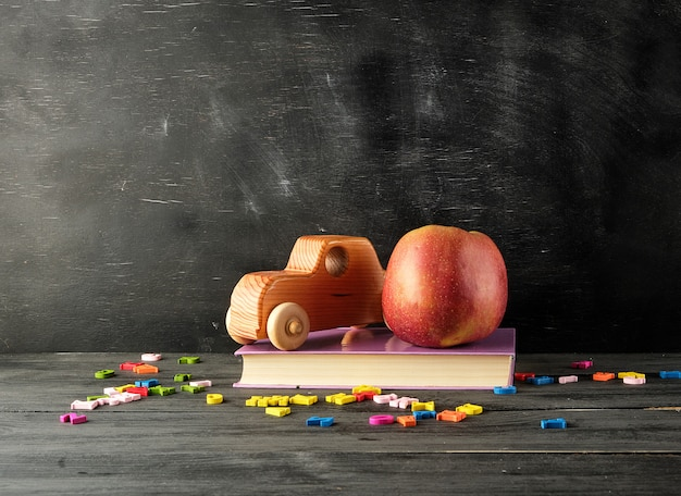 Ripe red apple,  ancient toy car stand on a book Premium Photo