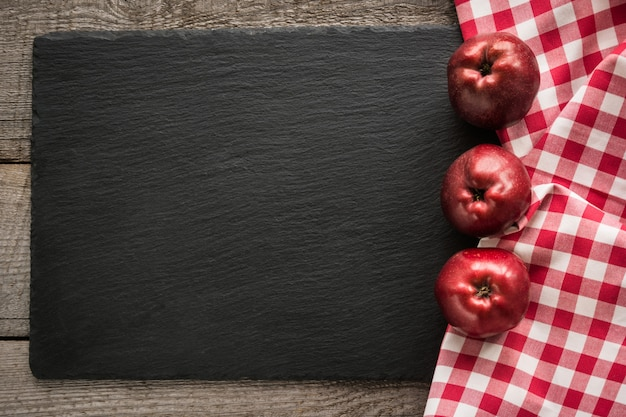 Ripe red apples on wooden board with red checkered napkin around Premium Photo