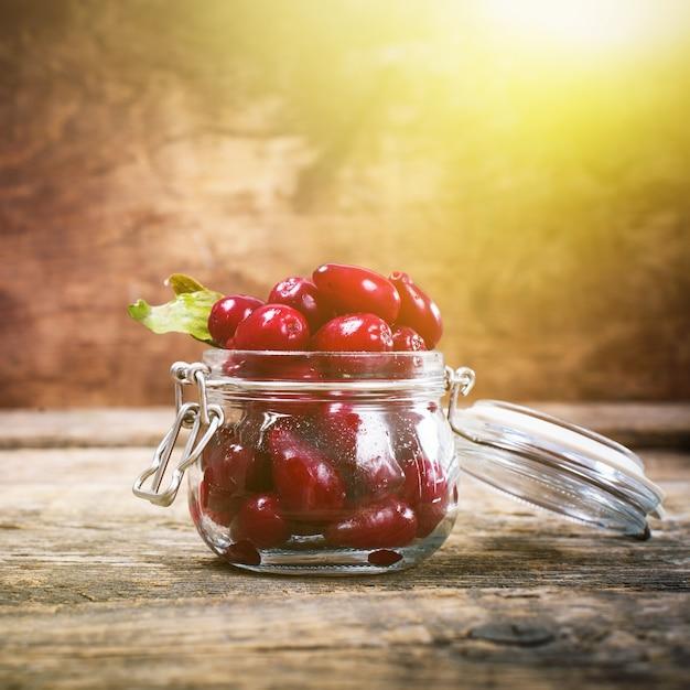 Спелые ягоды красного кизила в маленькой стеклянной банке Premium Фотографии