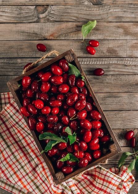 Спелый красный кизил на деревенском деревянном фоне Premium Фотографии