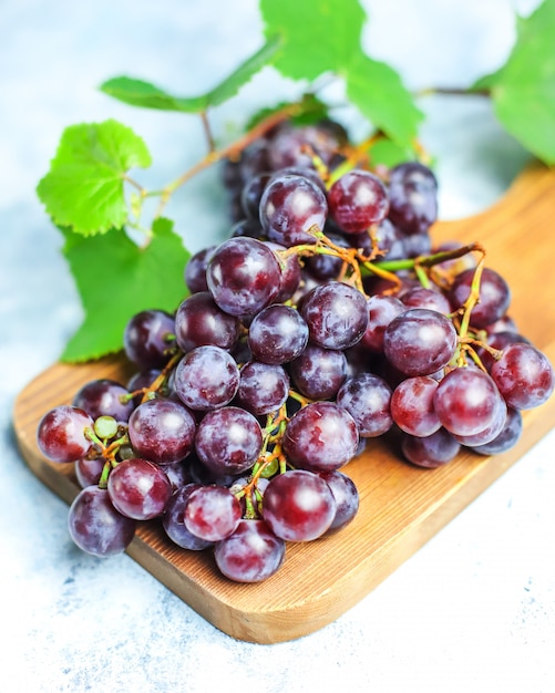 Ripe red grape with leaves on white . Free Photo