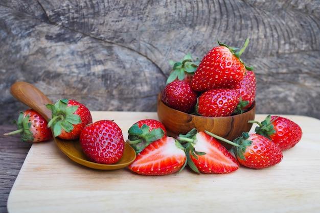 木製のテーブル背景に木製のボウルに熟した赤いイチゴ Premium写真