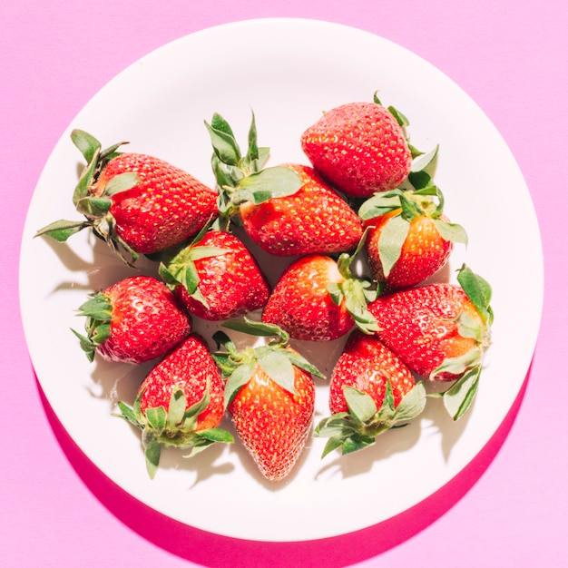 Ripe red strawberry with green stem on plate Free Photo