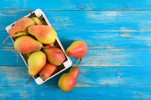 Спелые розовые груши в деревянном ящике на синем Premium Фотографии