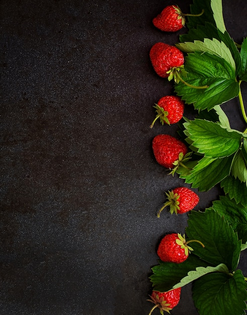 Ripe strawberries and leaves on black background. top view Free Photo