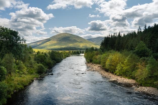 스코틀랜드의 나무와 산을 흐르는 강 무료 사진
