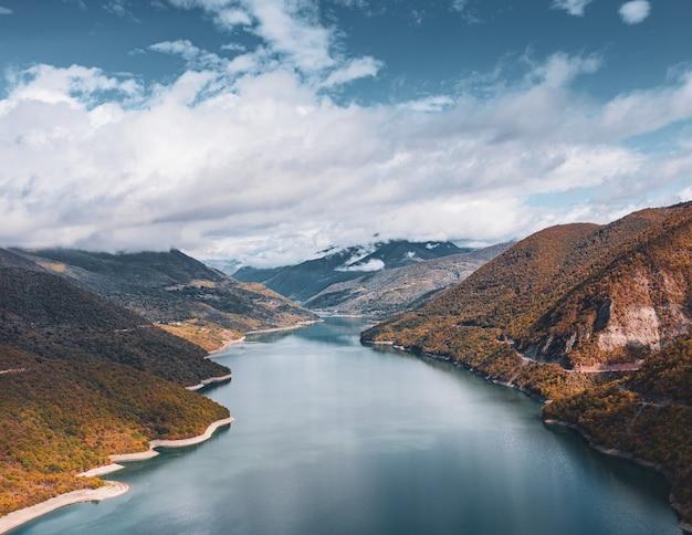 숨막히는 흐린 하늘 아래 언덕을 통과하는 강 무료 사진