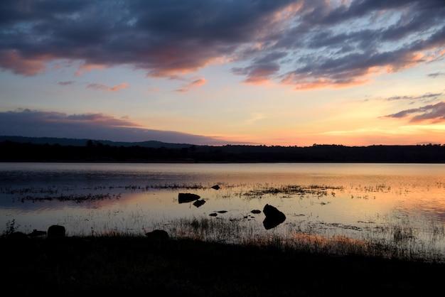 River and mountain landscape on sunset orange background Premium Photo