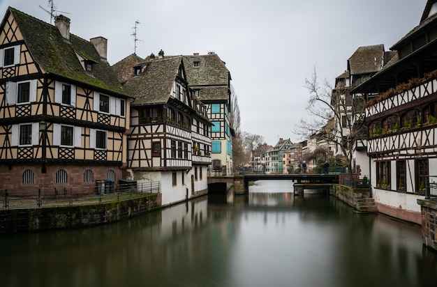 River surrounded by buildings in petite france under a cloudy sky in strasbourg in france Free Photo
