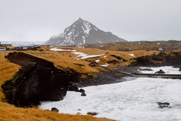 緑に覆われた丘とアイスランドの村の雪に囲まれた川 無料写真