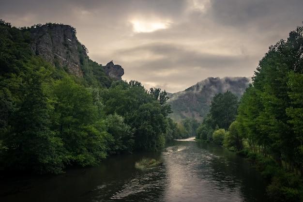 Река в окружении скал, покрытых мхом, и лесов под солнечным светом и облачным небом Бесплатные Фотографии