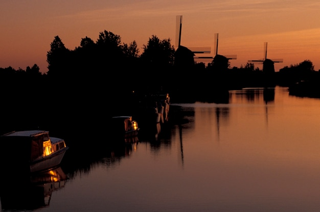 River and windmills at sunset, holland Premium Photo