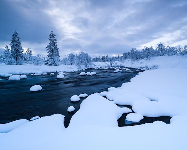 Fiume con neve in esso e una foresta vicino ricoperta di neve in inverno in svezia Foto Gratuite