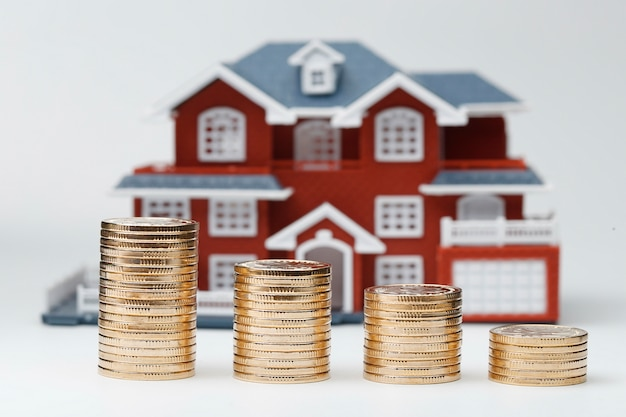 Rmb coins stacked in front of the housing model (house prices, house buying, real estate, mortgage concept) Free Photo