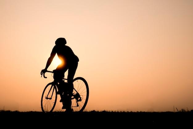 Road bike cyclist man cycling. biking sports fitness athlete riding bike on an open road Premium Photo