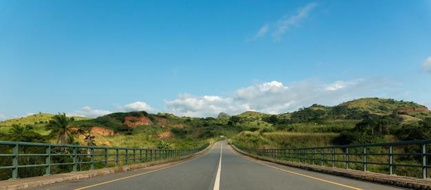 アンゴラのケベ川に架かる丘と緑に囲まれた道路橋 無料写真