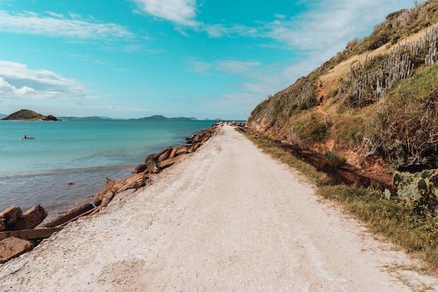 Дорога, покрытая песком, окруженная морем и скалами под голубым небом в рио-де-жанейро Бесплатные Фотографии