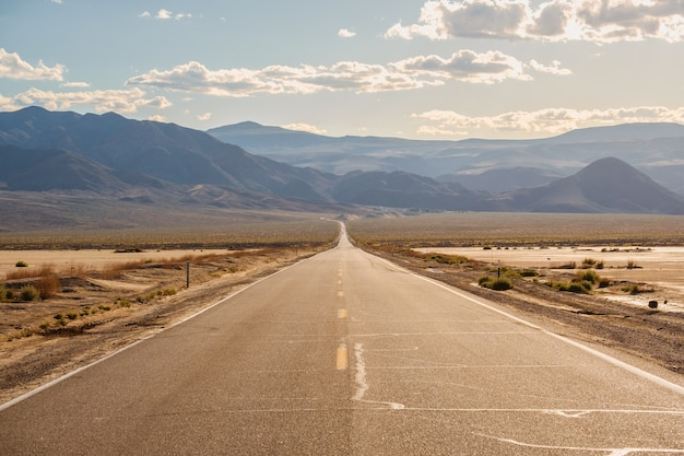 Road in the middle of the desert with the magnificent mountains in california Free Photo