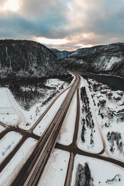 Дорога у реки и горы, покрытая снегом в дневное время Бесплатные Фотографии