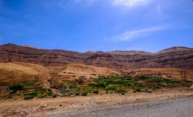 遠くに砂浜の山々と青い空と草原の近くの道路 無料写真