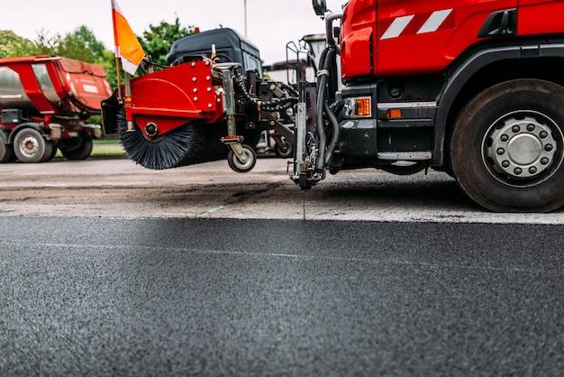 Road repair work. dusting machine while repairing road. street cleaning machine. Premium Photo