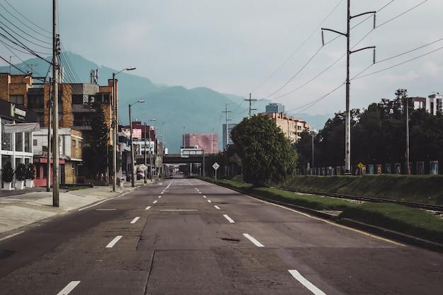 Strada immersa nel verde e edifici con montagne sotto la luce del sole Foto Gratuite