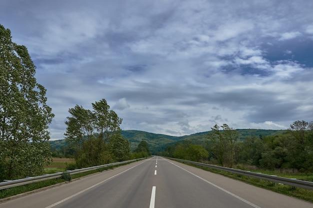 Strada circondata da colline coperte di boschi sotto il cielo nuvoloso durante il giorno Foto Gratuite